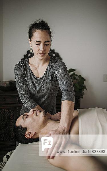 weibliche Massagetherapeutin behandelt männlichen hispanischen Patienten