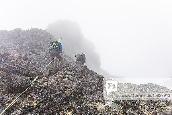 Aufblick zu zwei Männern  die sich im Nebel von einer Bergklippe abseilen
