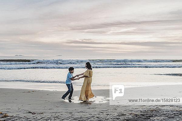 Landschaft mit Mutter und Sohn beim Spielen am Wasser während des Sonnenuntergangs