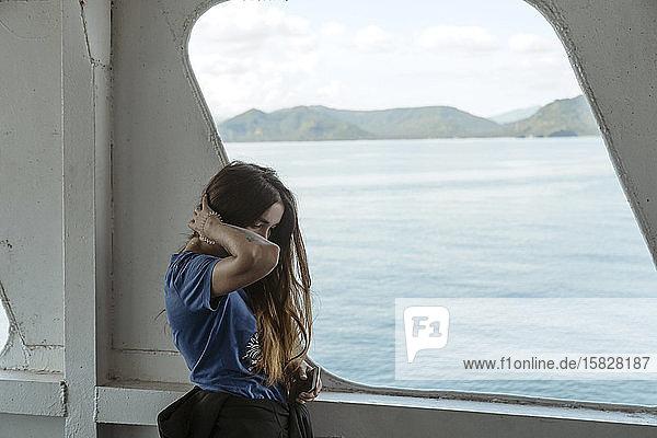 Seitenansicht einer Frau  die durch ein Bootsfenster hinaussieht