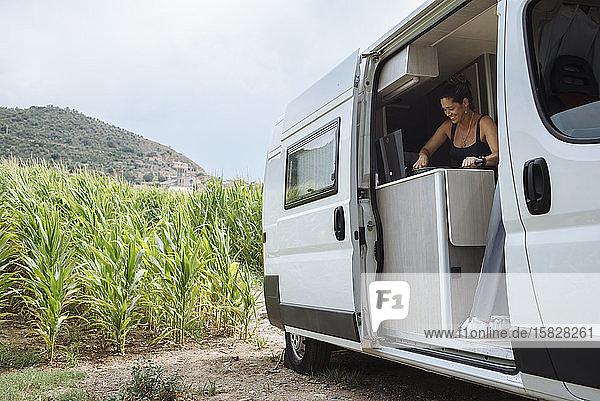 Frau mit Brötchen beim Geschirrspülen im Wohnmobil während eines Urlaubs.