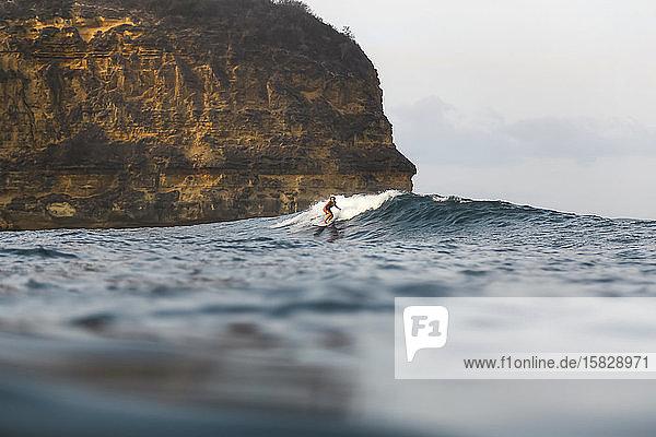 Junge Frau beim Surfen im Indischen Ozean