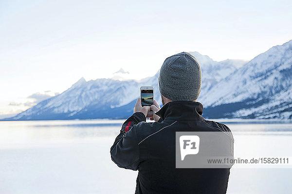 Mann macht mit einem Smartphone ein Foto von Jackson Lake und Teton Range