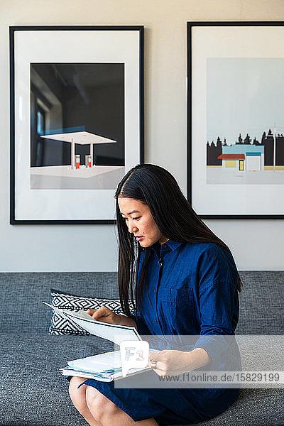 Junge Geschäftsfrau liest Dokumente  während sie im Büro auf dem Sofa sitzt