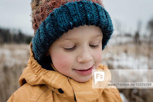 Nahaufnahme eines Jungen  der lächelnd nach unten schaut  während er draußen spielt