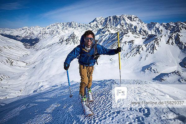 Lächelnder Mann fährt Skitouren auf einer Piste mit Bergen im Rücken