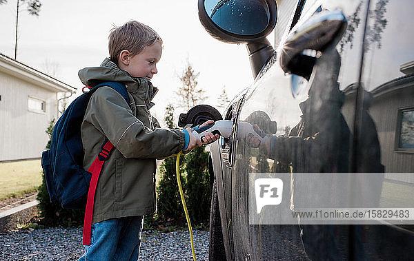ein Junge  der vor der Schule das Elektroauto der Familie anschließt