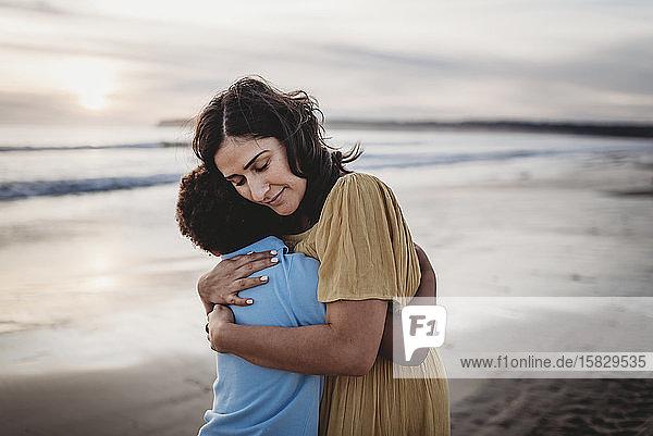 Seitenansicht einer schönen Mutter  die ihren Sohn bei Sonnenuntergang am Meeresufer umarmt
