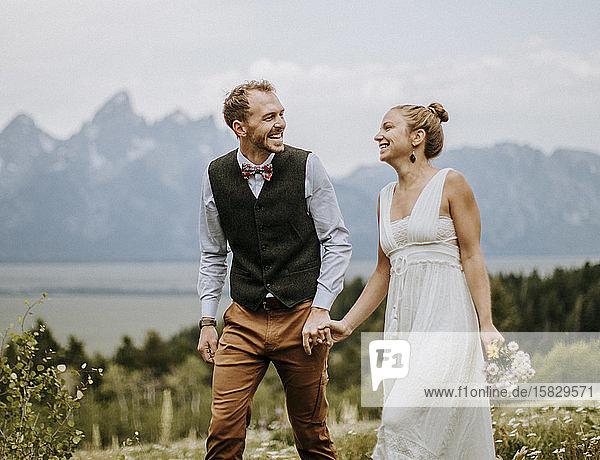 Lachende Frischvermählte halten sich beim Spaziergang in den felsigen Bergen Wyomings an den Händen