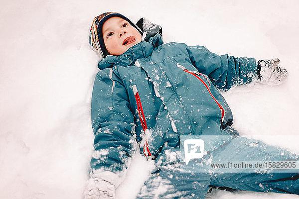 Glücklicher Junge mit ausgestreckten Armen im Winter im Schnee liegend