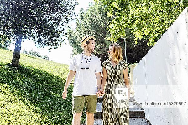 Glückliches junges Paar geht in einem Park spazieren und hält sich an den Händen
