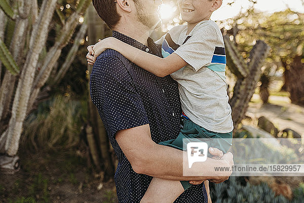 Mid view of father holding older son and smiling at each other