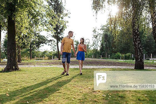 Junges Paar geht Hand in Hand  um im Park Badminton zu spielen
