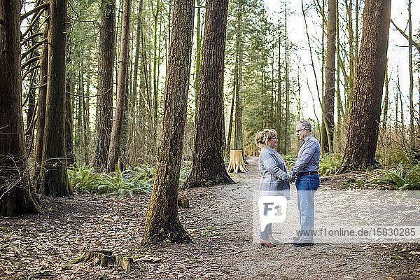 Älteres Paar  das sich im Wald an den Händen hält und einander anschaut.