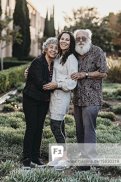 Porträt eines aktiven älteren Ehepaares und einer erwachsenen Tochter lächelnd