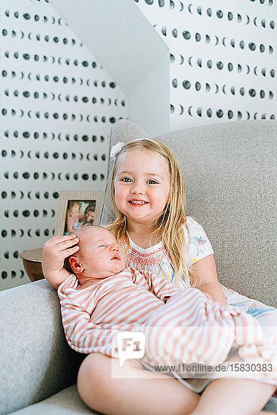 Geradeaus auf dem Portrait eines jungen Mädchens  das seine kleine Schwester hält