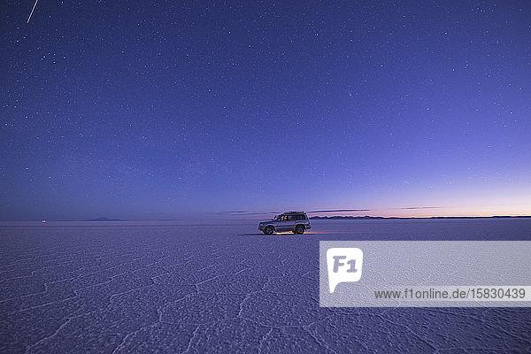 vehicle on salar de uyuni at sunset