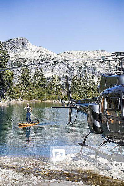 Aktive Frau paddelt auf einem abgelegenen See  zu dem ein Hubschrauber Zugang hat.