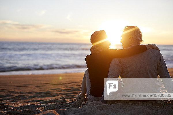 Rückansicht eines älteren Ehepaares,  das bei Sonnenuntergang am Strand im Sand sitzt