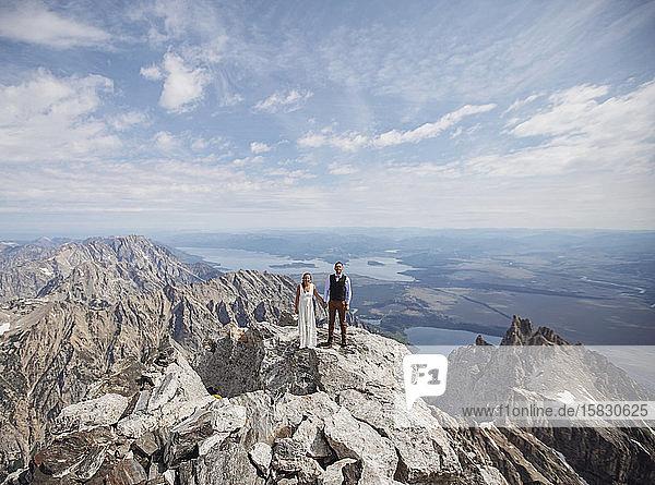 Braut und Bräutigam stehen auf dem Gipfel des Grand Teton  nachdem sie geheiratet haben.