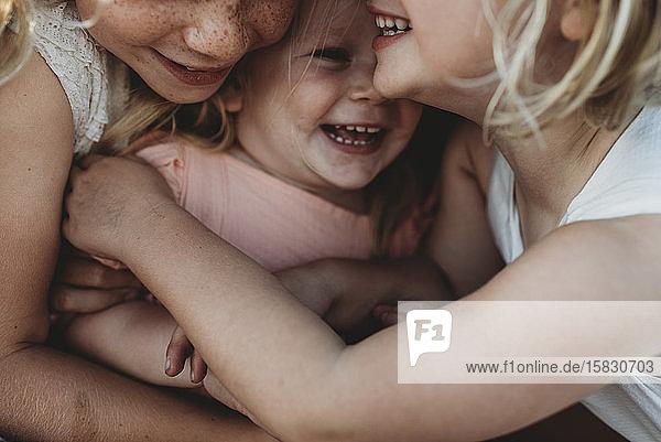 Nahaufnahme eines lachenden Kleinkindes umgeben von jungen Schwestern