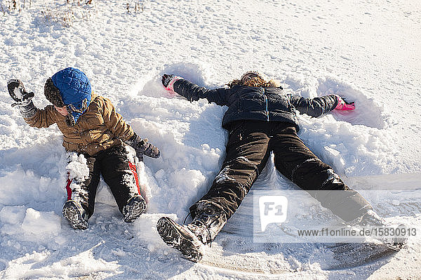 Brother and Sister playing in the snow in front yard