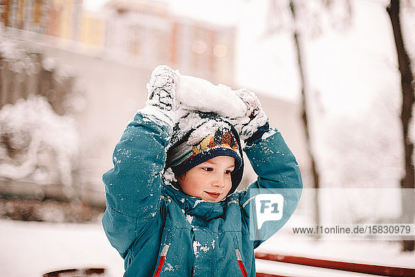 Happy boy playing with snow during winter