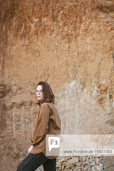 Lifestyle-Porträt einer jungen  modischen Frau in ungewöhnlicher Landschaft