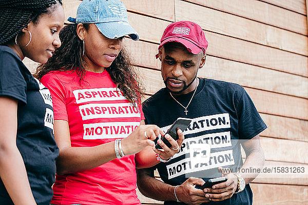 Gruppe diverser Freunde steht an der Wand und schaut auf ein Smartphone