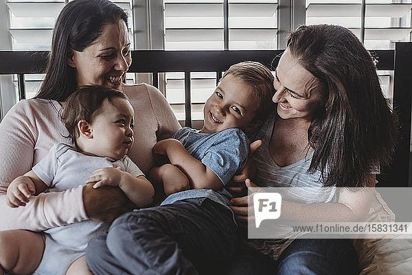 Familie mit zwei Müttern  die zu Hause lachen und kuscheln