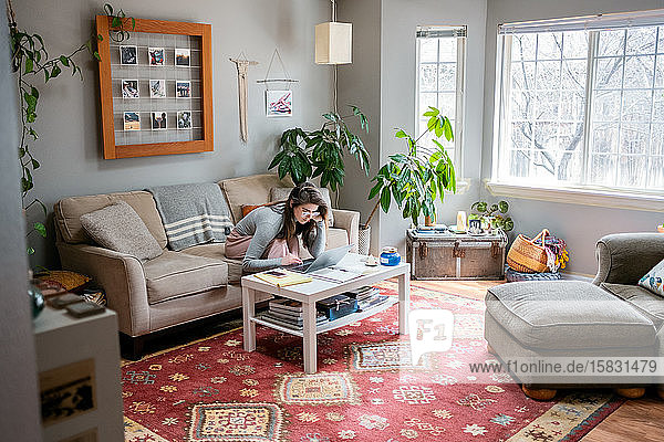 Junge Frau  die während COVID von zu Hause aus arbeitet 19