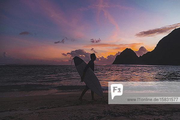 Surfer am Strand zur Zeit des Sonnenuntergangs
