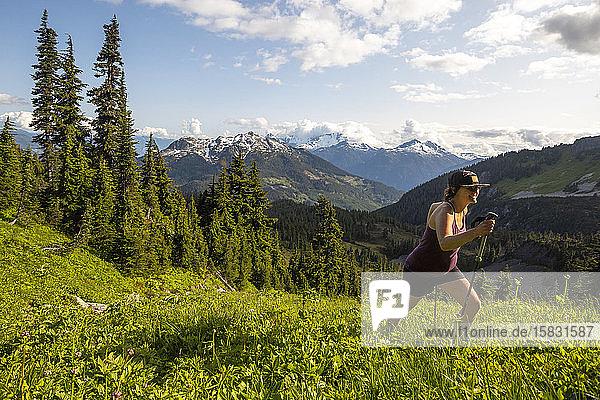 Eine schwangere Frau wandert an einem sonnigen Tag in den Bergen.