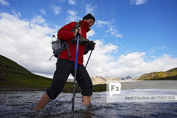 junge Frau überquert Fluss auf dem Laugavegur-Wanderweg
