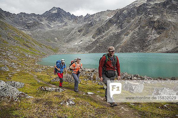 Menschen wandern am Ufer des Upper Reed Lake  Talkeetna-Gebirge  Alaska