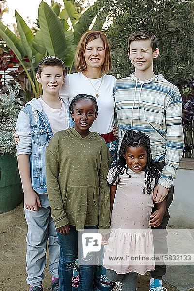 Smiling multiracial siblings and mid-40's mom hugging near lush plants
