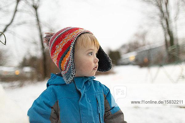 Seitenansicht Porträt eines Kleinkindes mit Strickmütze draussen im Schnee