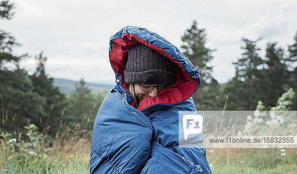 Porträt einer in einen Schlafsack gehüllten Frau  die wild im Freien zeltet