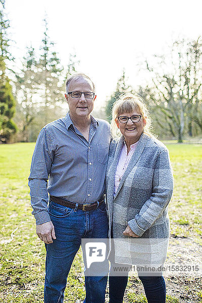 Portrait of happy elderly couple in a park setting.