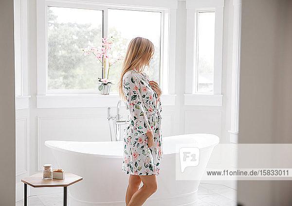 Junge Frau in der Nähe der Badewanne