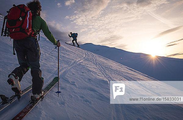 Zwei Personen bei Sonnenaufgang beim Skilanglauf in Island
