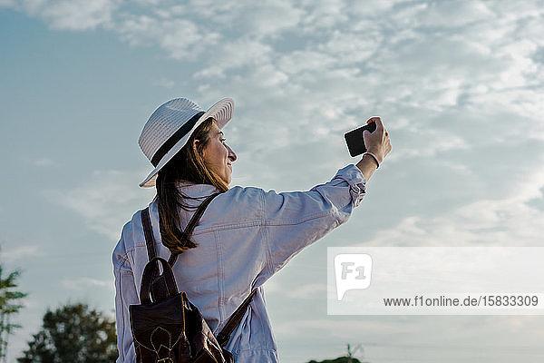 Junge Frau nimmt mit ihrem Smartphone ein Selbstporträt auf. Reisen  Lebensstil