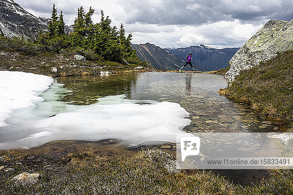 A women jumps over water on the edge of an alpine pool on summer day in the mountains of British Columbia.
