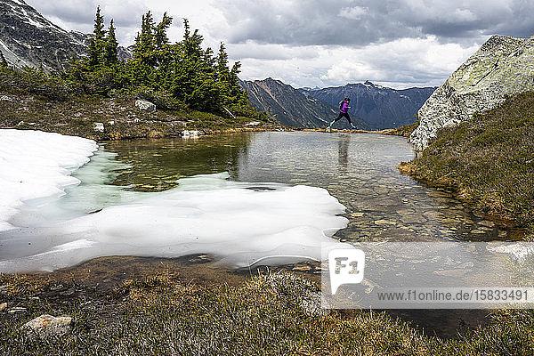 Eine Frau springt an einem Sommertag in den Bergen von Britisch-Kolumbien am Rand eines alpinen Pools über Wasser.