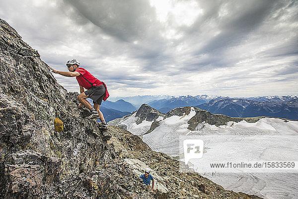 Zwei Bergsteiger klettern eine Felsklippe in den Bergen hinauf.