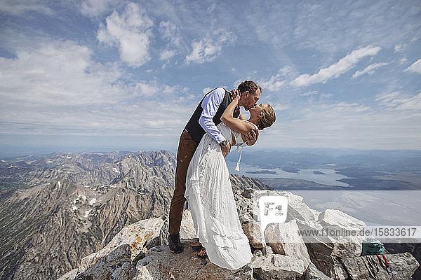 Bräutigam taucht Braut nach Heirat auf dem Gipfel des Berges