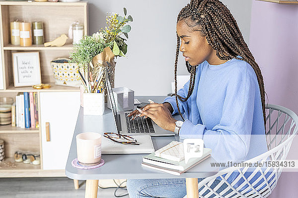 Junges Mädchen schreibt und arbeitet zu Hause mit dem Computer
