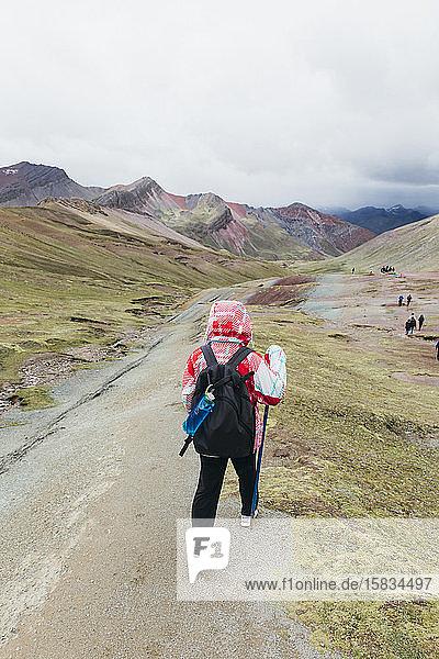 Eine junge Frau wandert auf den berühmten Regenbogenberg in Peru