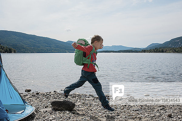 Junge springt mit einem Rucksack auf Felsen beim Camping am Meer