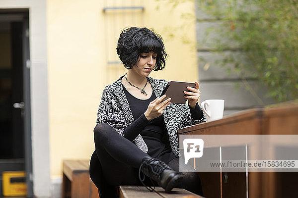 junge Frau mit Laptop im Freien bei der Arbeit